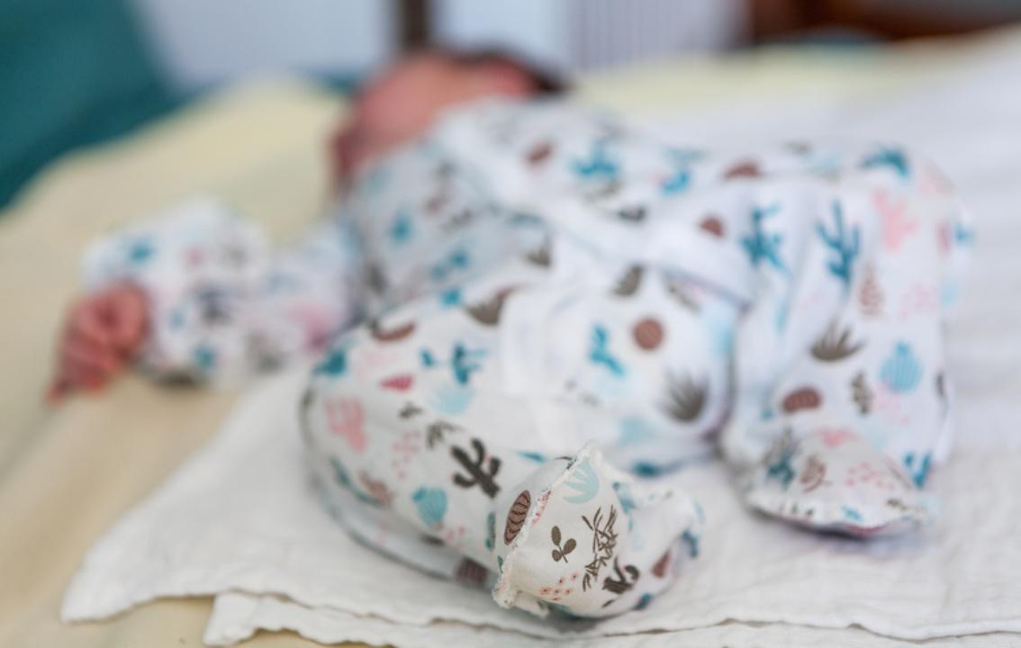 маленький ребенок в светлом боди спит на спине