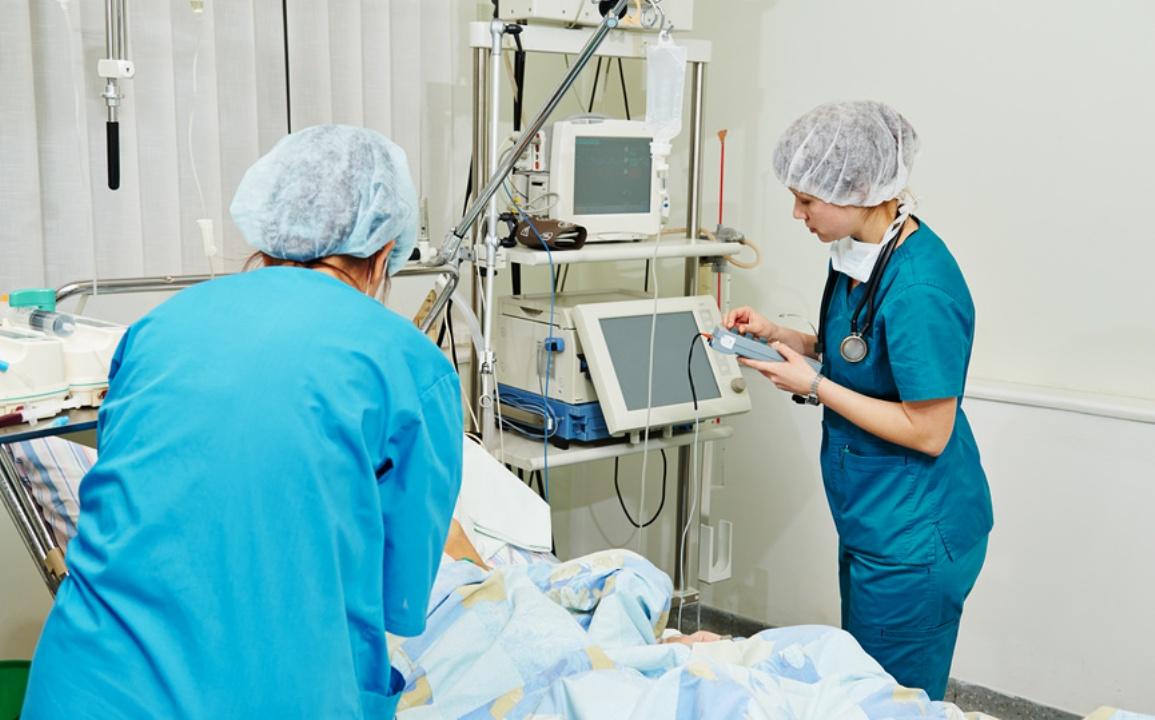 Две медсестры в голубой форме склонились над пациентом, который подключен к аппарату