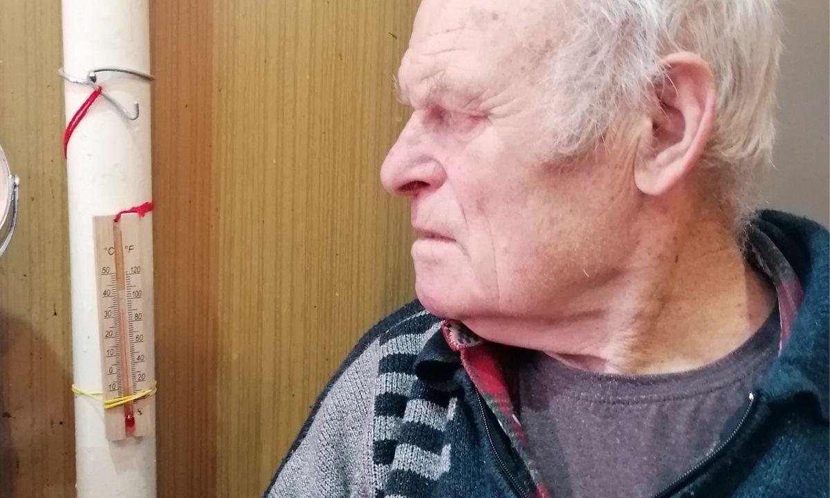 пенсионер смотрит на градусник