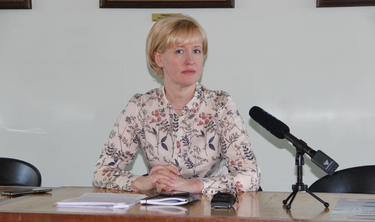 Женщина-блондинка в блузе с цветами сидит за столом с микрофоном