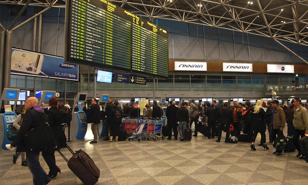 Зал отправления аэропорта Хельсинки. люди стоят в очереди на регистрацию. на переднем плане идет мужчина с чемоданом