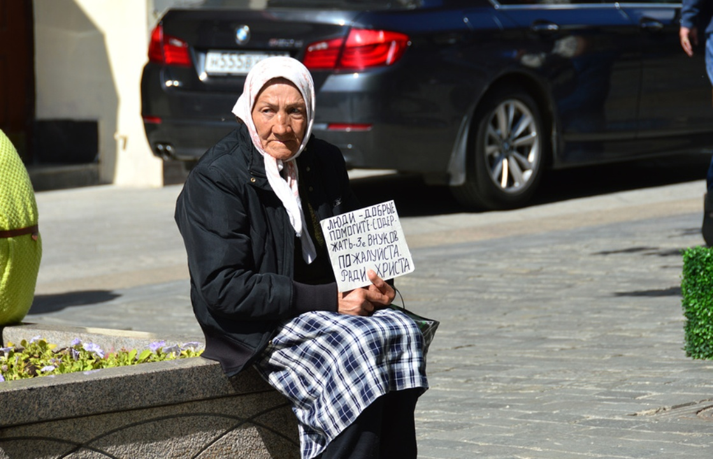 Нищая пожилая женщина просит милостыню на Кузнецком мосту в Москве
