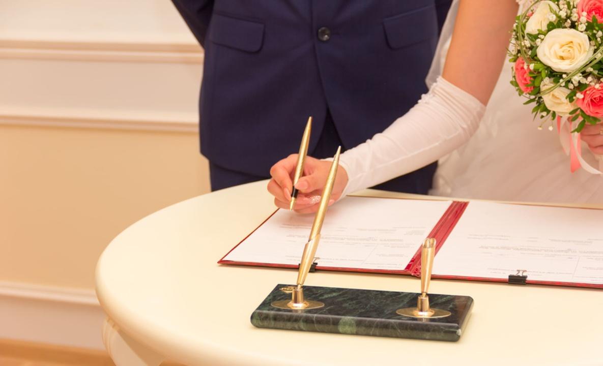 рука в белой перчатке держит ручку и подписывает документ