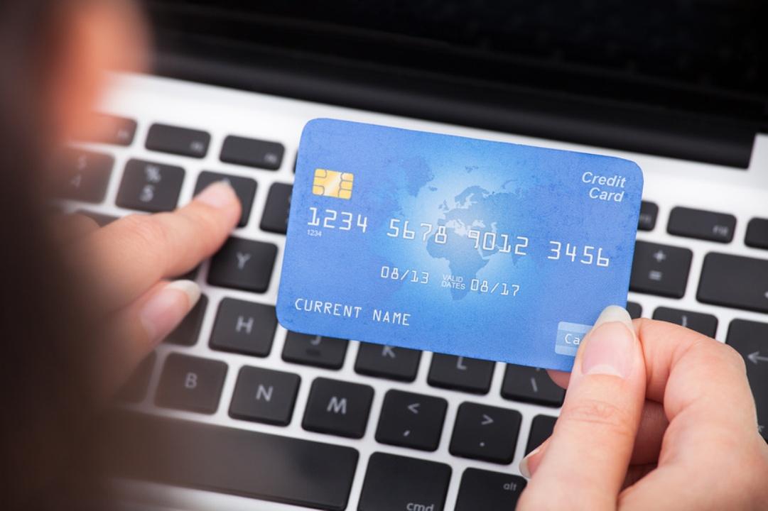 женщина держит банковскую карту и печатает на клавиатуре