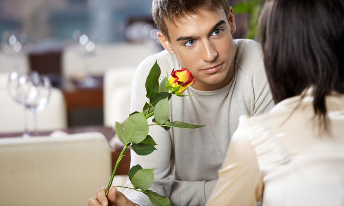 мужчина с розой в руках вместе с женщиной в кафе
