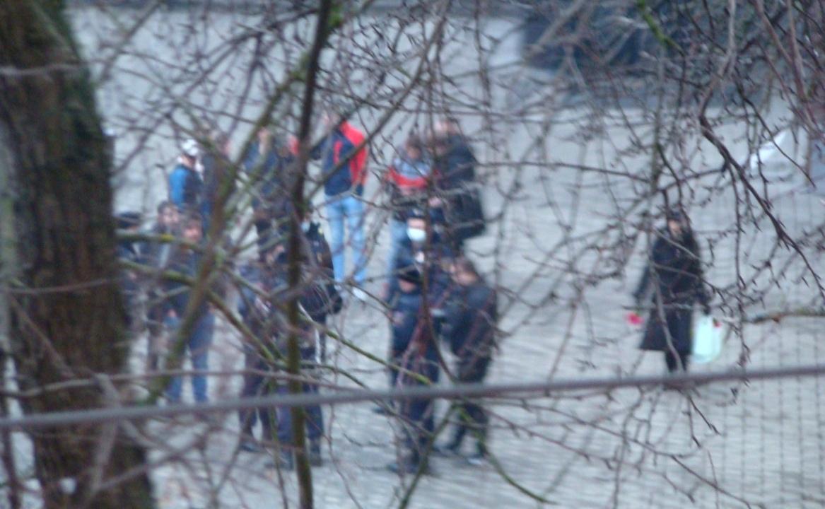 Толпа подросток стоит на улице в окружении полицейских