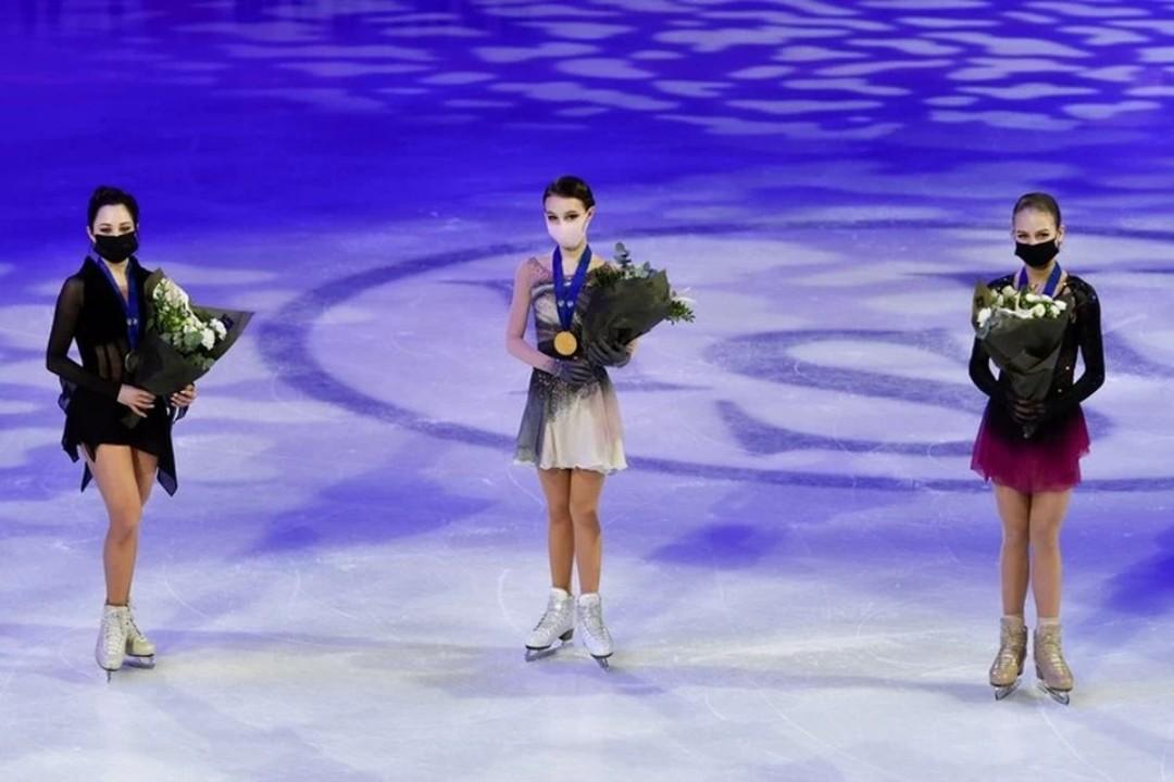 Три российские фигуристки стоят на ледовой арене с цветами