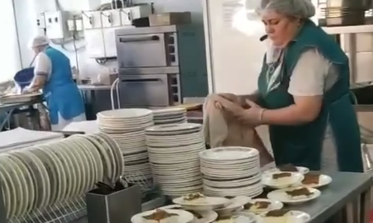 тарелки с едой стоят друг на друге, толстая женщина в форме повара вытирает руки тряпкой