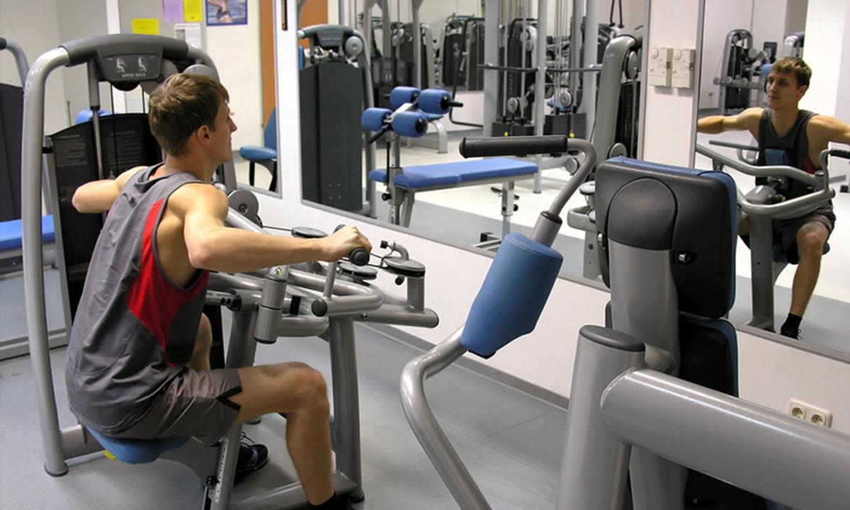 Мужчина в тренажерном зале делает упражнения на спину