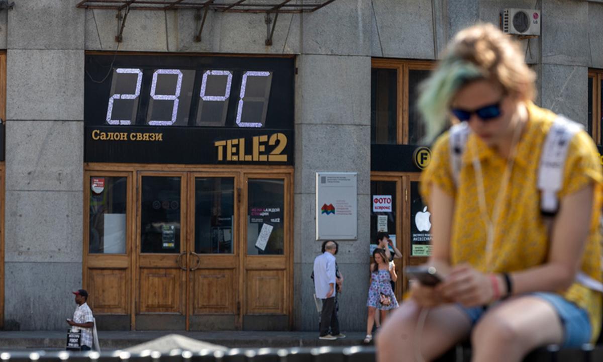 девушка сидит на улице у нее за спиной большое электронное табло, которое показывает температуру воздуха: 29 градусов