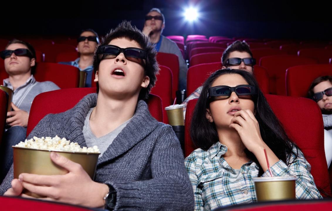 Молодые люди в кинотеатре сидят в красных креслах и в очках