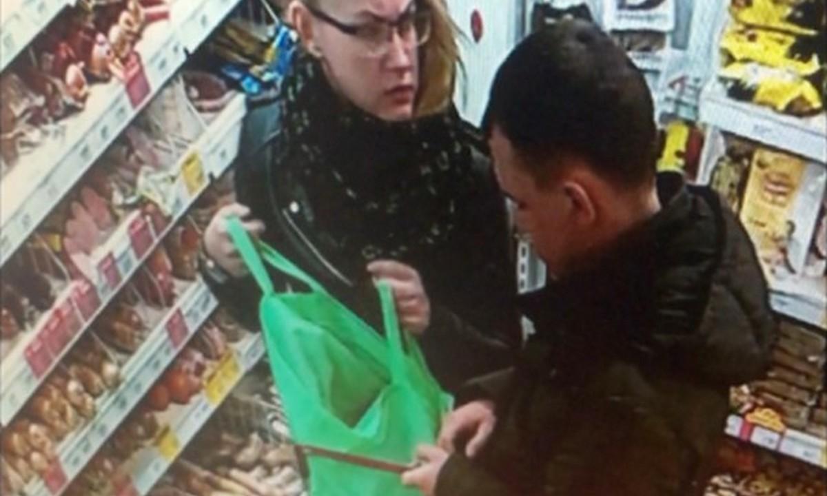 молодая пара ворует продукты в магазине