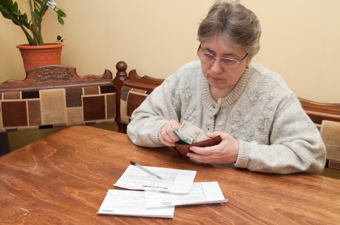 седовласая женщина сидит за столом со счетами за ЖКХ
