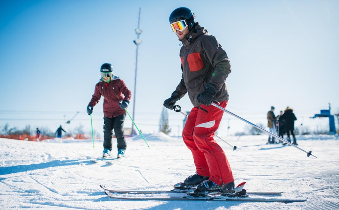Мужчина в красных штанах учится кататься на лыжах на склоне