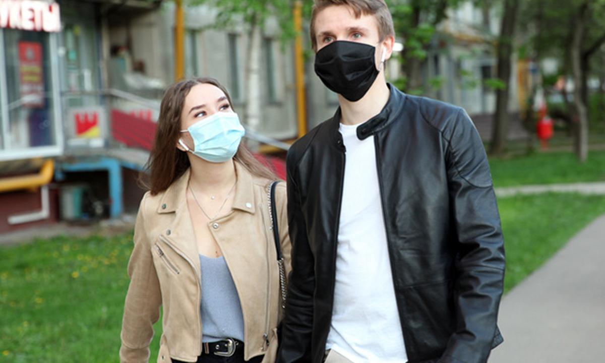 девушка и мужчина в защитных масках идут по улице