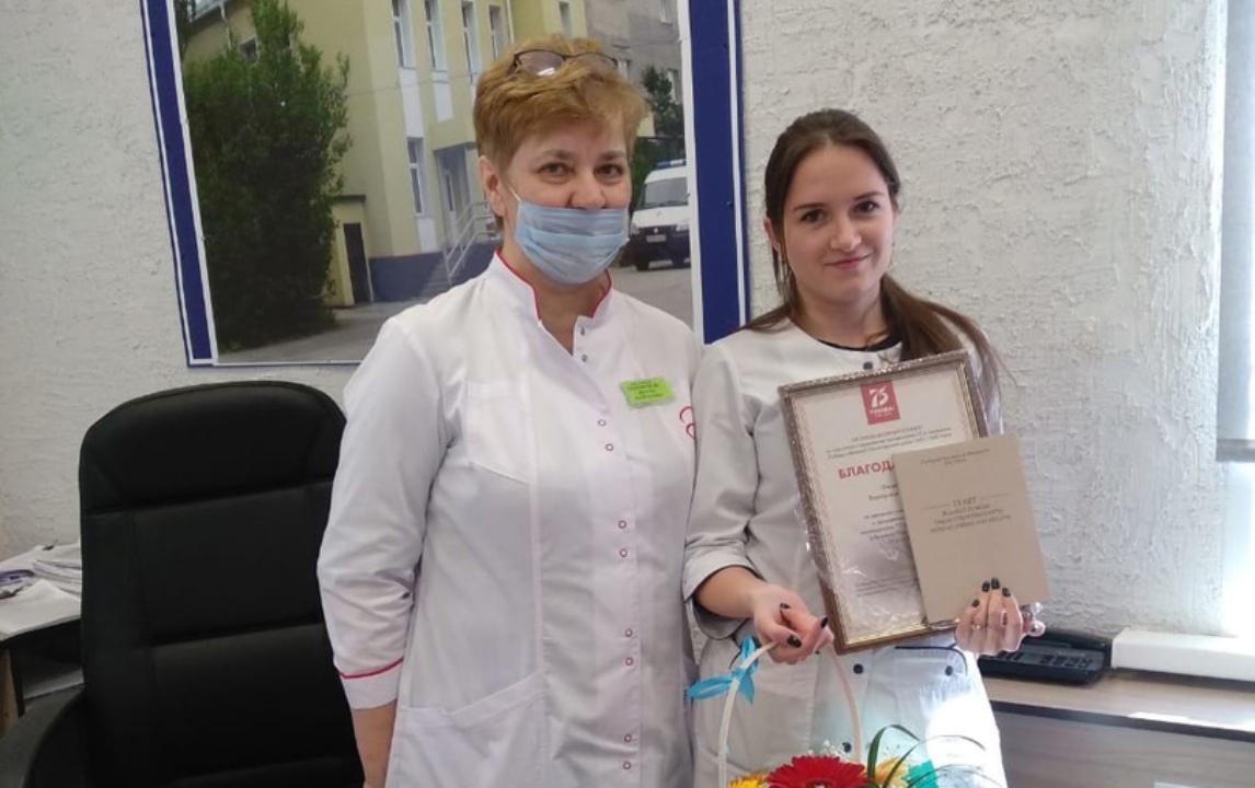 Два врача в белых халатах стоят рядом в кабинете с грамотой в руках