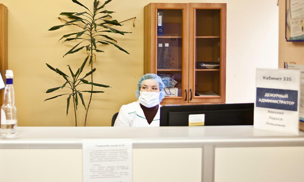 Женщина в маски и белом халате сидит в регистратуре