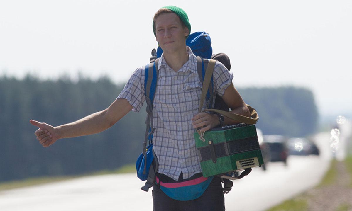 Молодой мужчина в рубашке и шапке стоит на трассе с поднятой вверх рукой