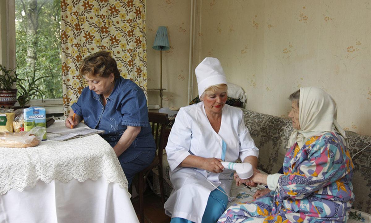 В квартире у пенсионерки сидит женщина за столом и заполняет документы, медик в белом халата проводит какие-то манипуляции с рукой пенсионерки. Пенсионерка сидит на диване