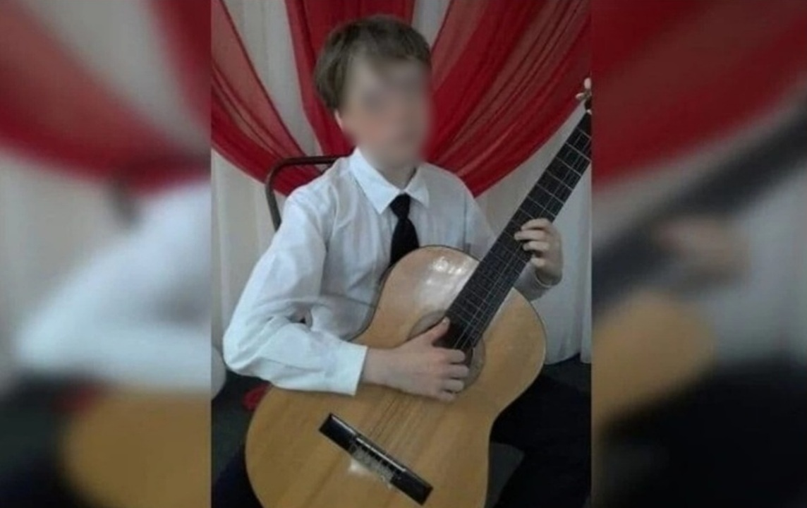 подросток в белой рубашке сидит с гитарой в руках