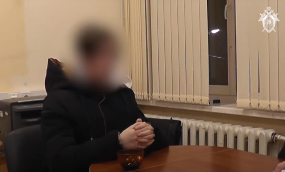Подросток в черной кофте сидит за столом в Следкоме и держит руки скрещенными