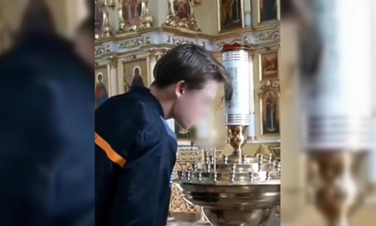 подросток прикуривается от свечи в храме