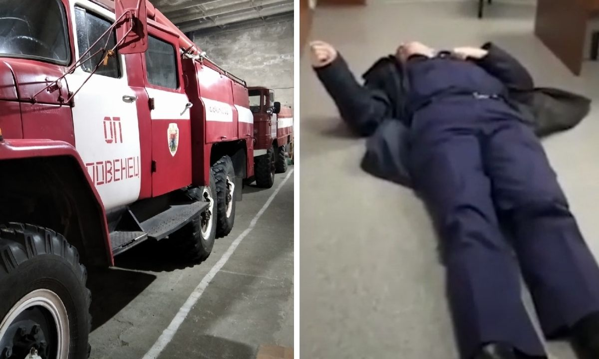 Мужчина в синей форме лежит на полу, и красная пожарная машина стоит в гараже