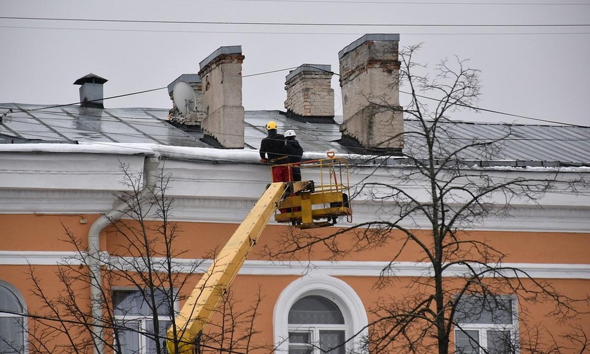 рабочие чистят крышу