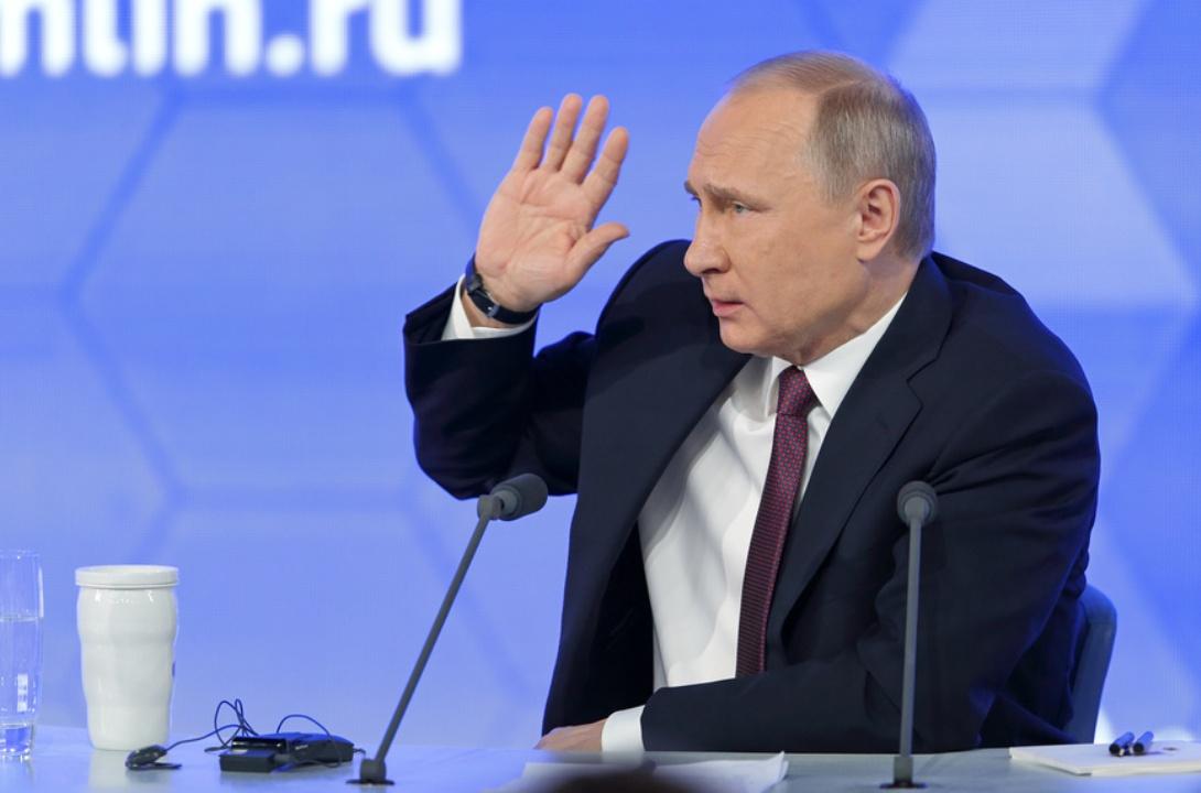 Владимир Путин сидит за столом на синем фоне