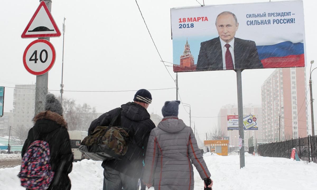 билборд с портретом Путина, под рекламой конструкцией стоят школьники спиной к камере