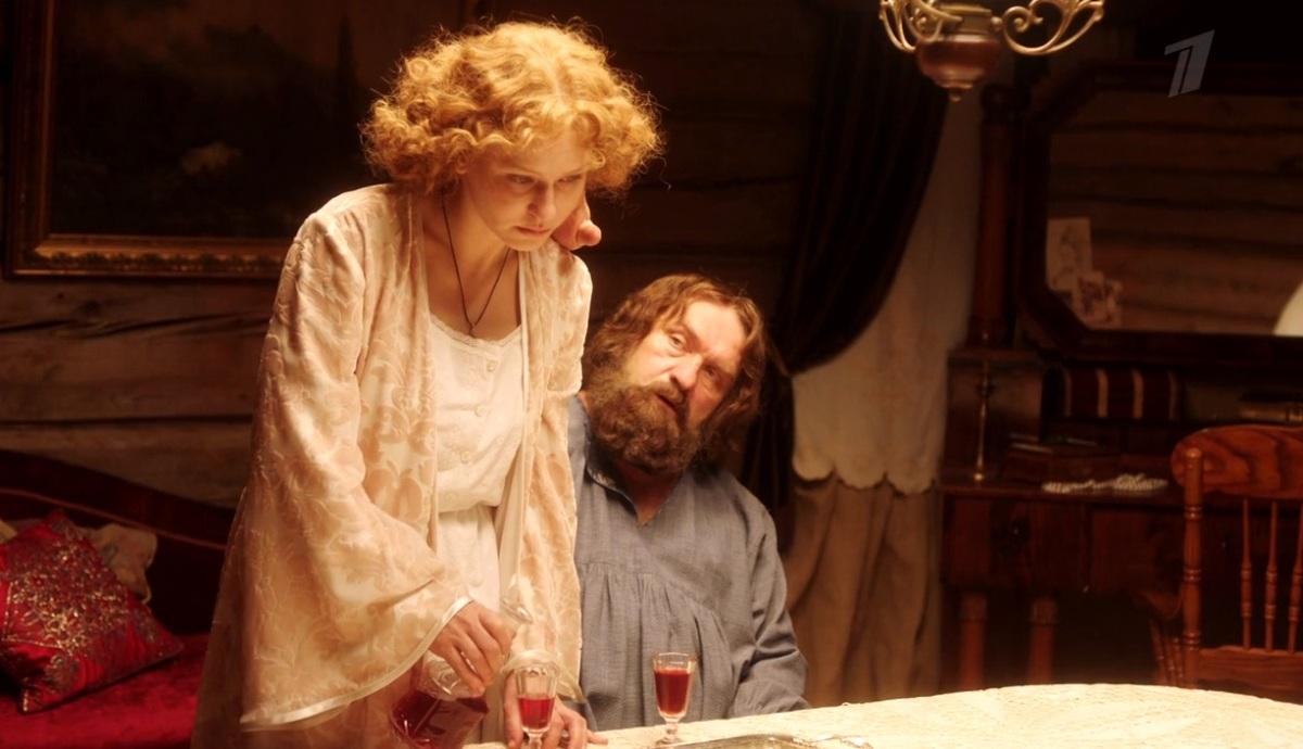 Белокурая женщина в белой сорочки стоит в комнате, а бородатый мужчина сидит и гладит ей щеку