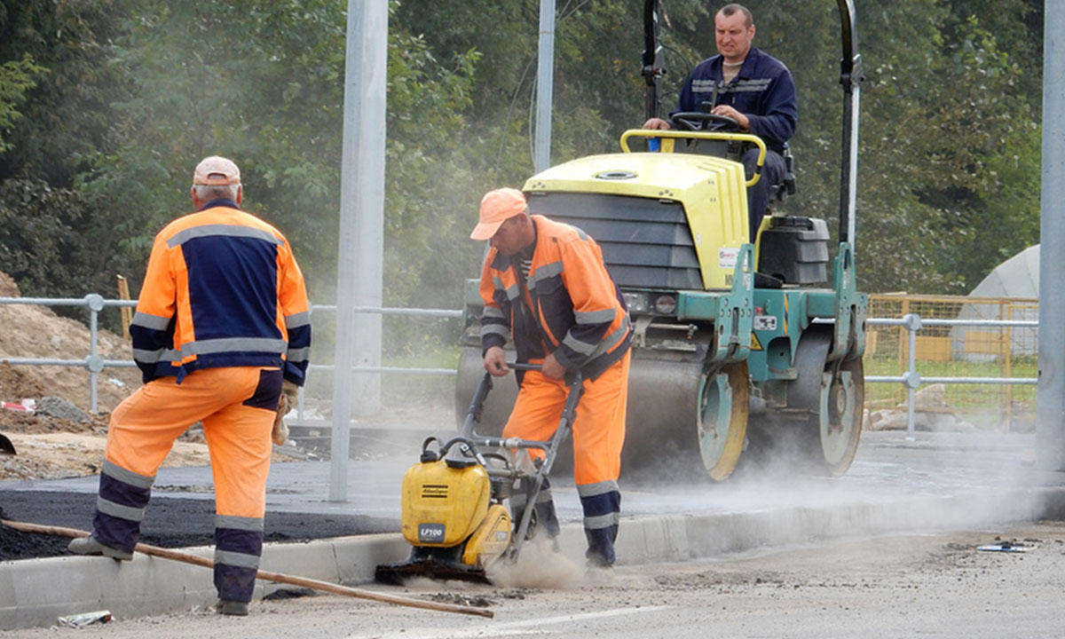 Бригада рабочих укладывает асфальтовое покрытие на дороге