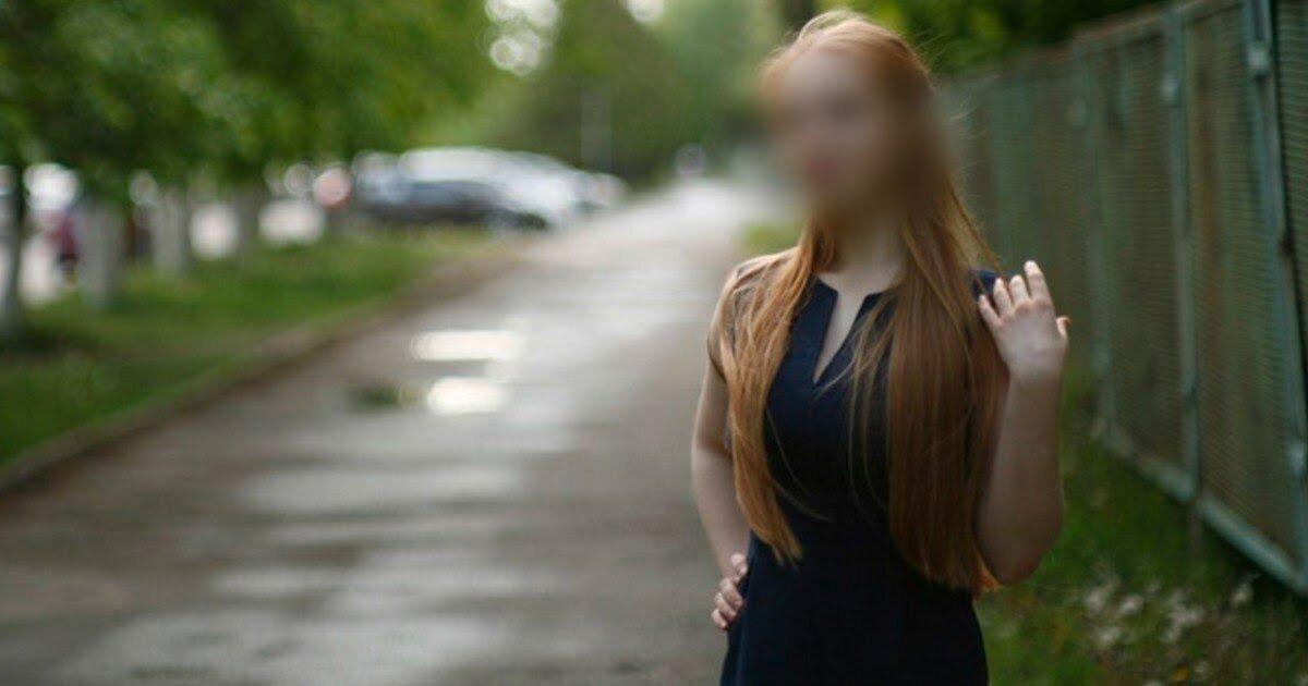 Девушка с рыжими волосами и в черном платье стоит на летней улице