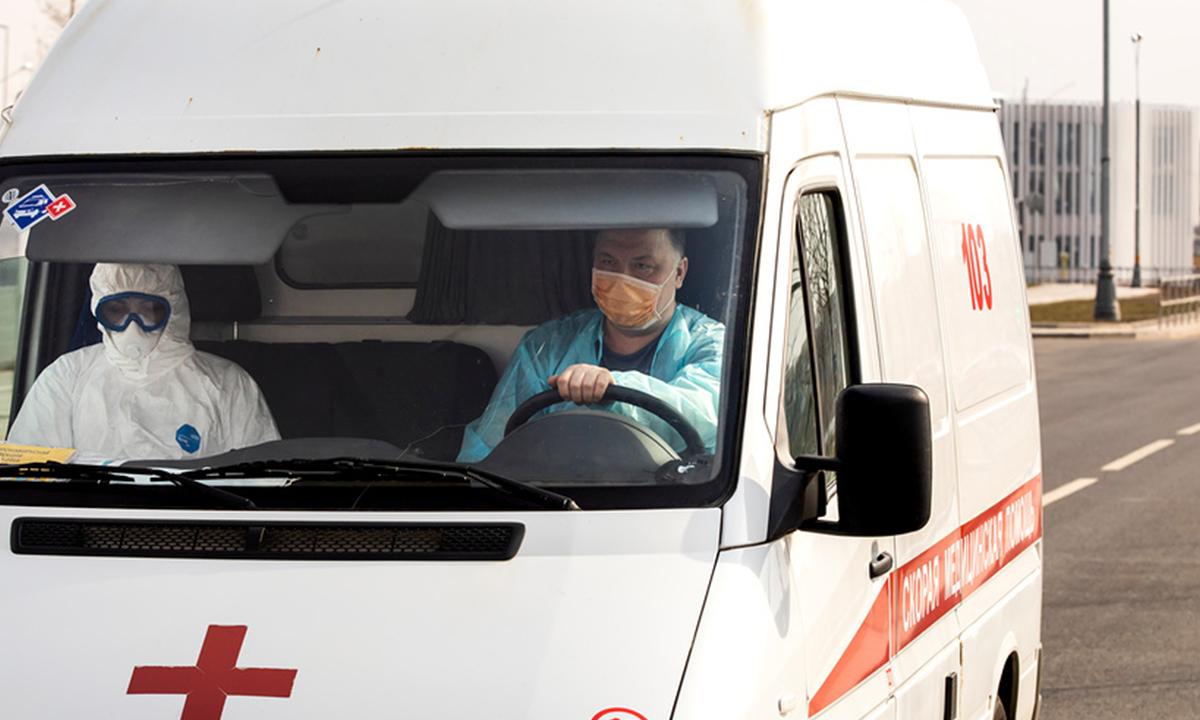 машина скорой помощи, в которой сидит водитель и врач в защитном костюме