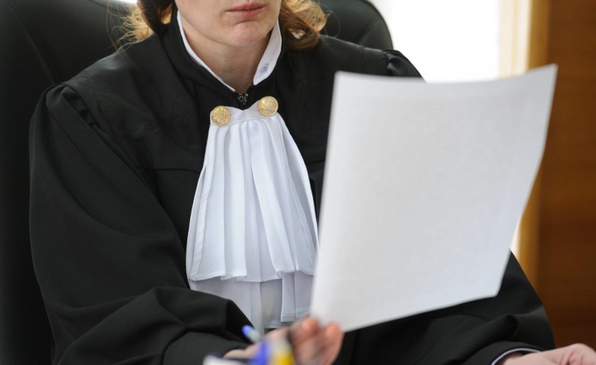 Женщина-судья в черной мантии сидит за столом и держит в руках лист бумаги