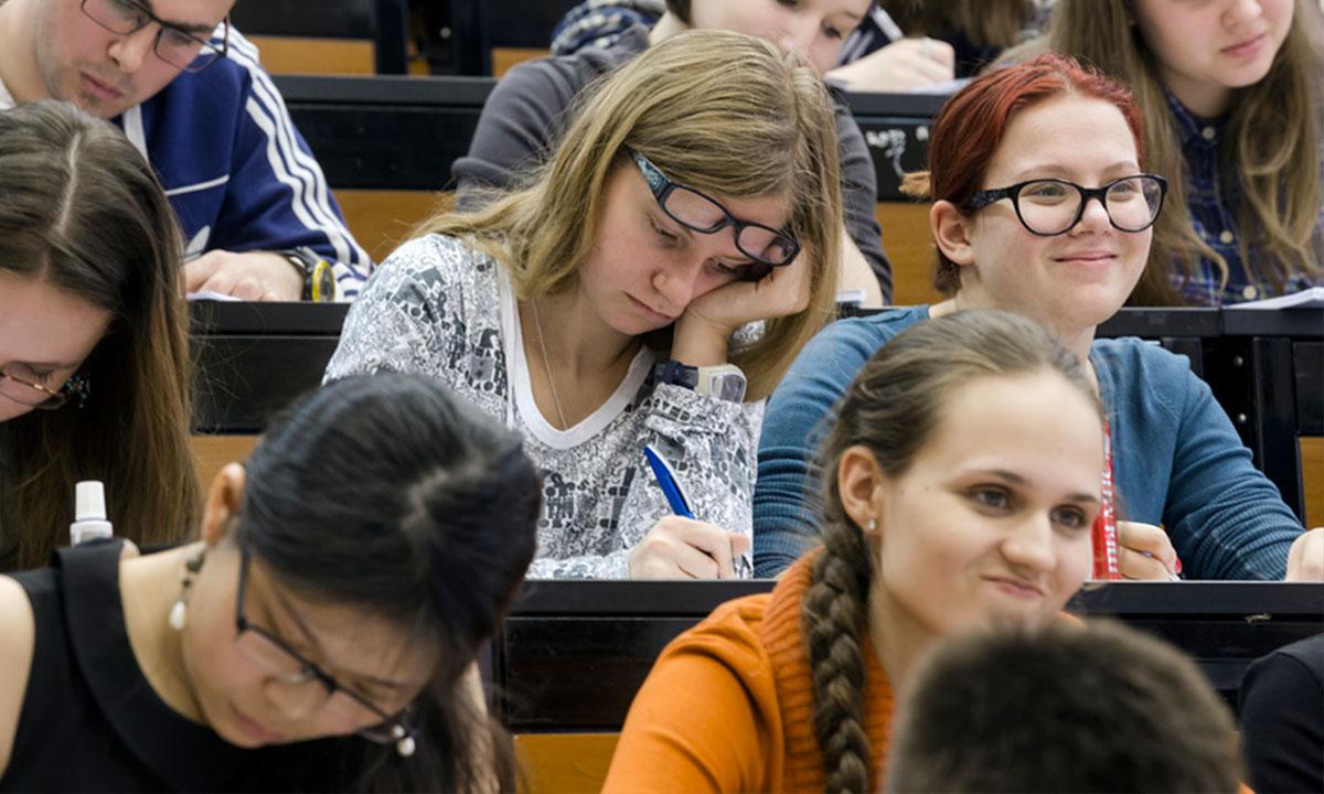 Молодые люди усердно пишут контрольную в аудитории