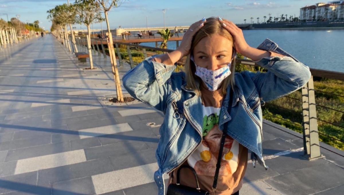 Девушка в маске гуляет по набережной