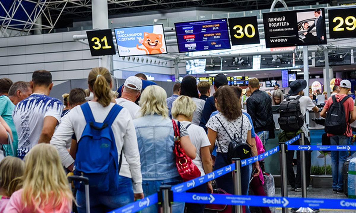 Люди стоят в плотной очереди к стойке регистрации в аэропорту