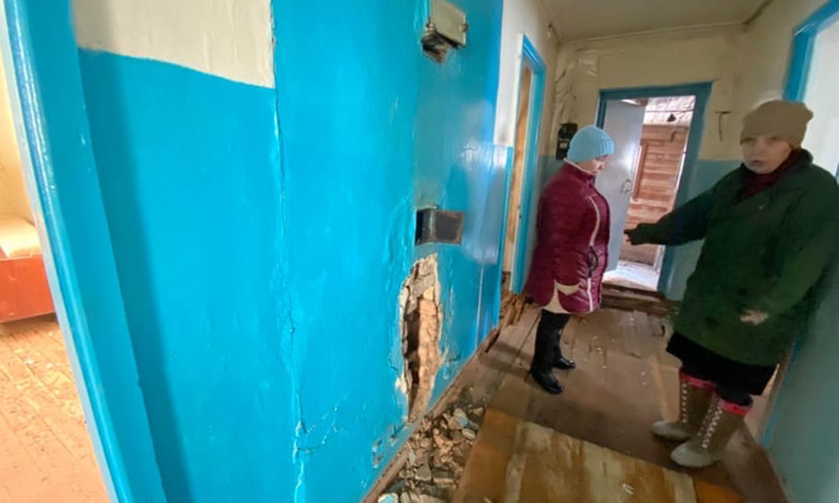 женщина в аварийном доме показывает на дыру в стене