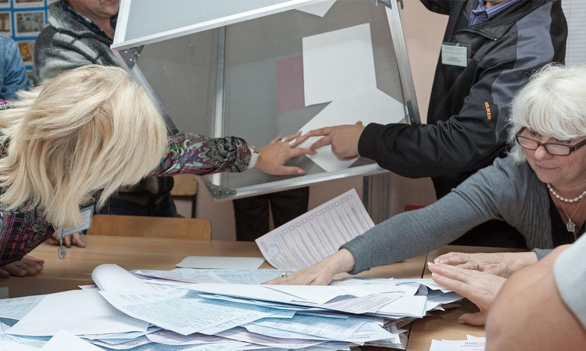 Члены избирательной комиссии вытряхивают на стол бюллетени из урны для голосования