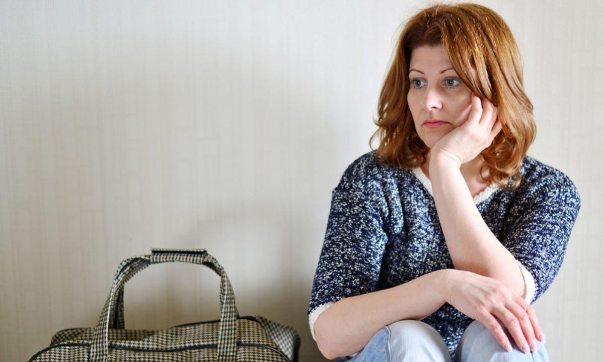 женщина грустит у чемодана