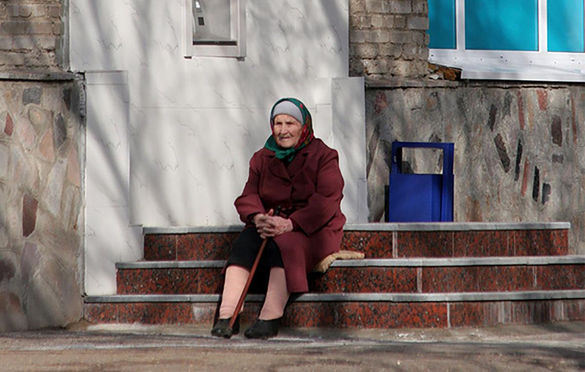 Пнсионерка сидит на ступеньках у банкомата