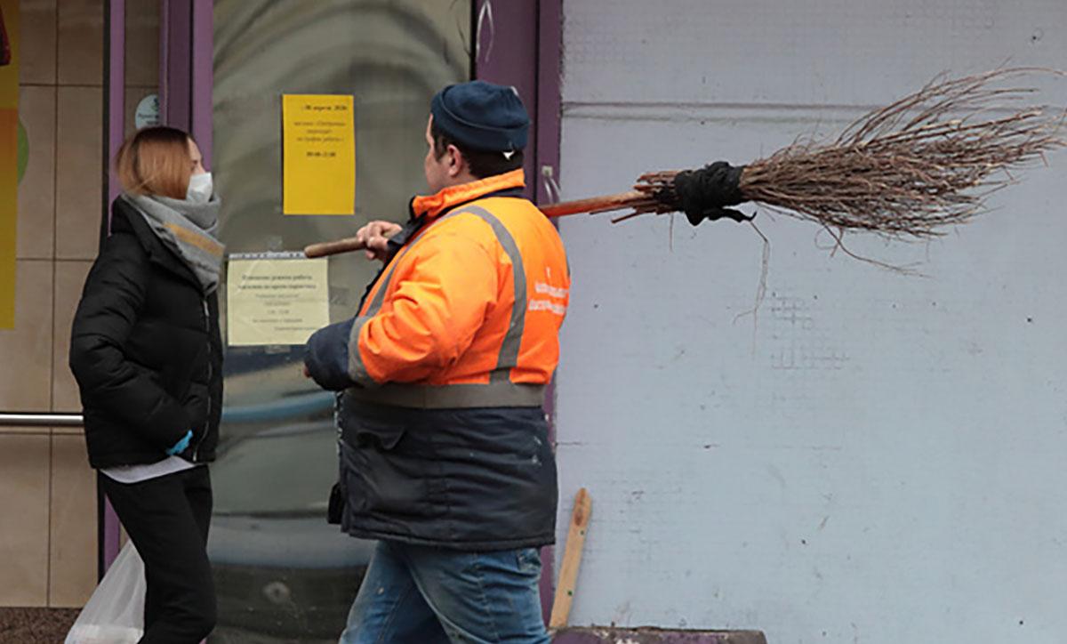Дворник идет с метлой по улице