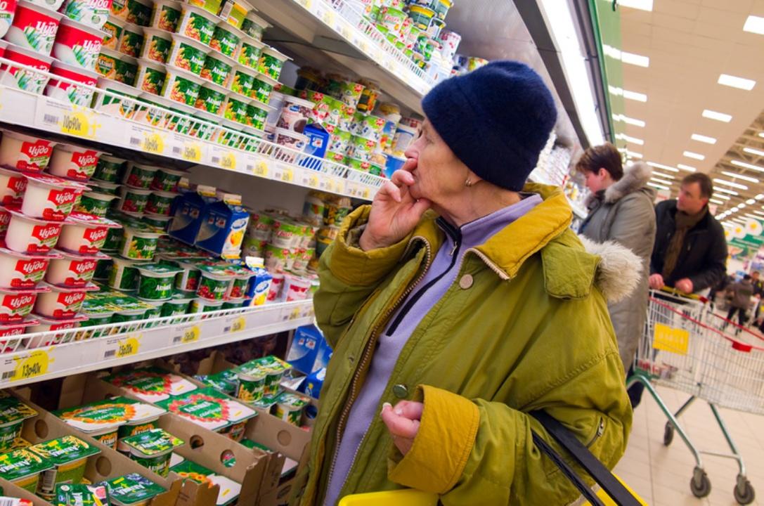 Пожилая женщина возле полок с йогуртом