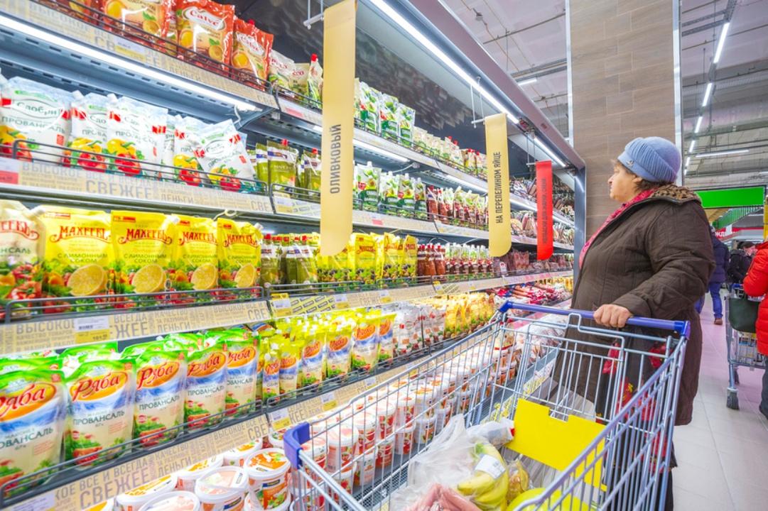 Женщина выбирает майонез в магазине