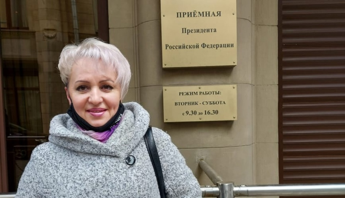 Женщина в сером пальто стоит на улице и улыбается