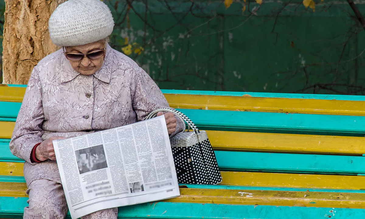 Пенсионеры получать дополнительную выплату в апреле. Старушка на скамейке читает газету
