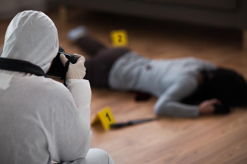 Криминалист фотографирует убитую женщину