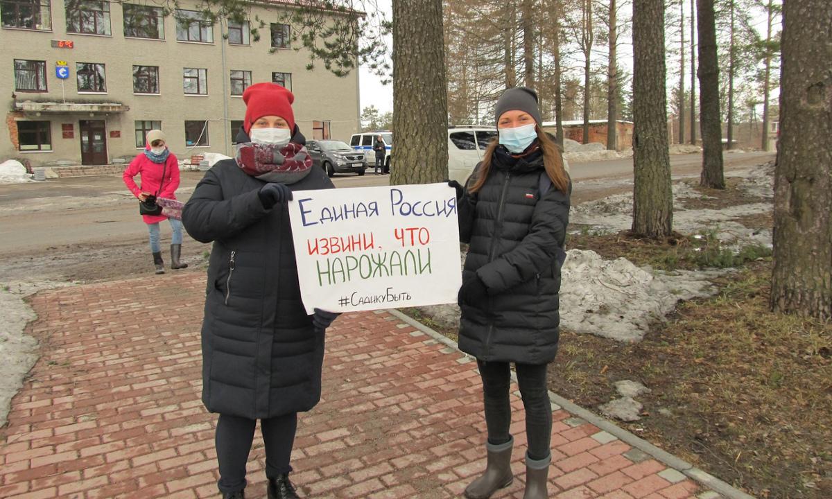Девушки с плакатом на митинге