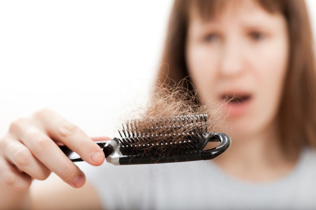 Женщина смотрит на выпавшие волосы, которые собрались на расческе